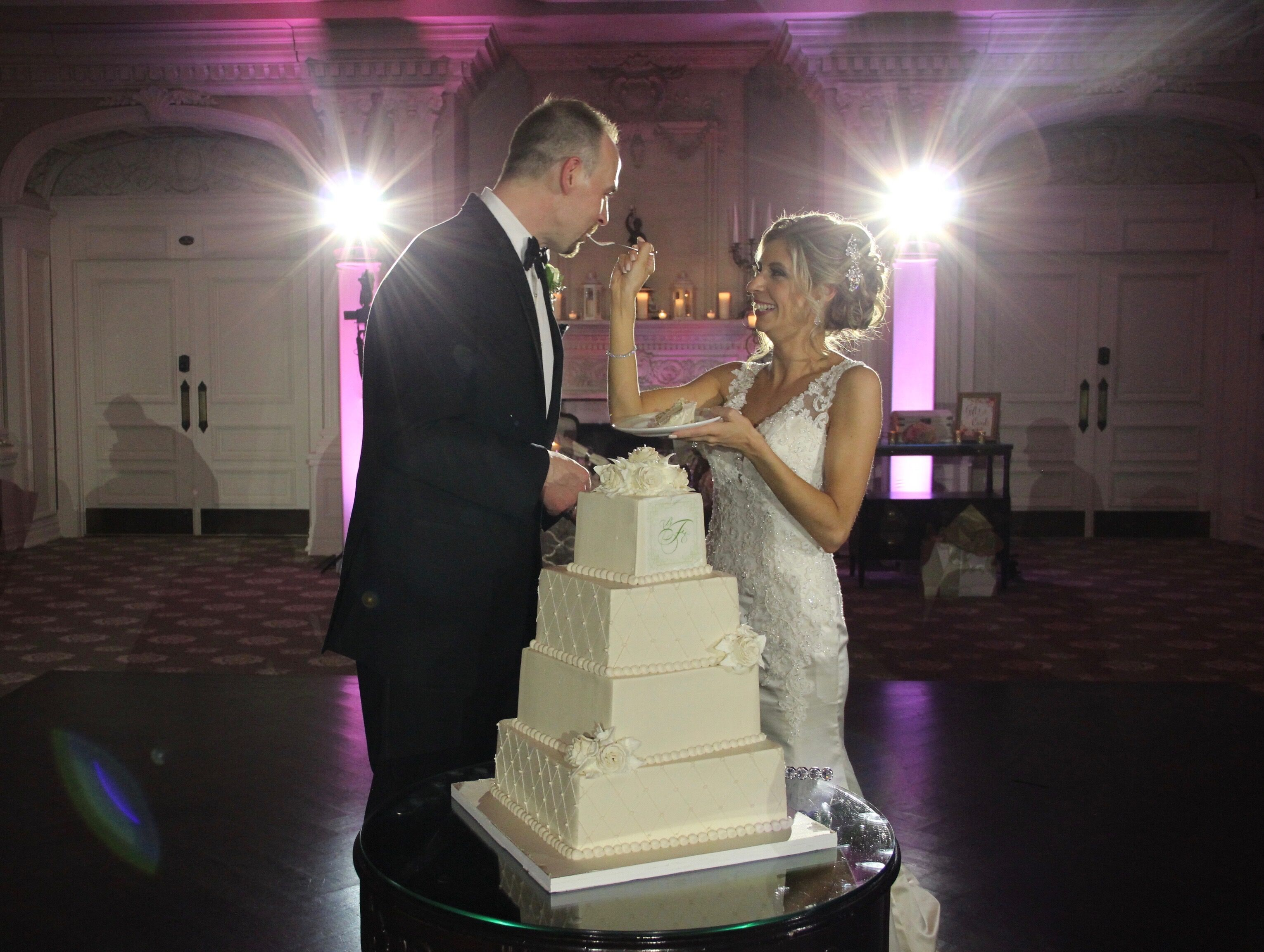 Bride and groom feed each other wedding cake surrounded by intelligent lighting towers at Park Savoy, NJ