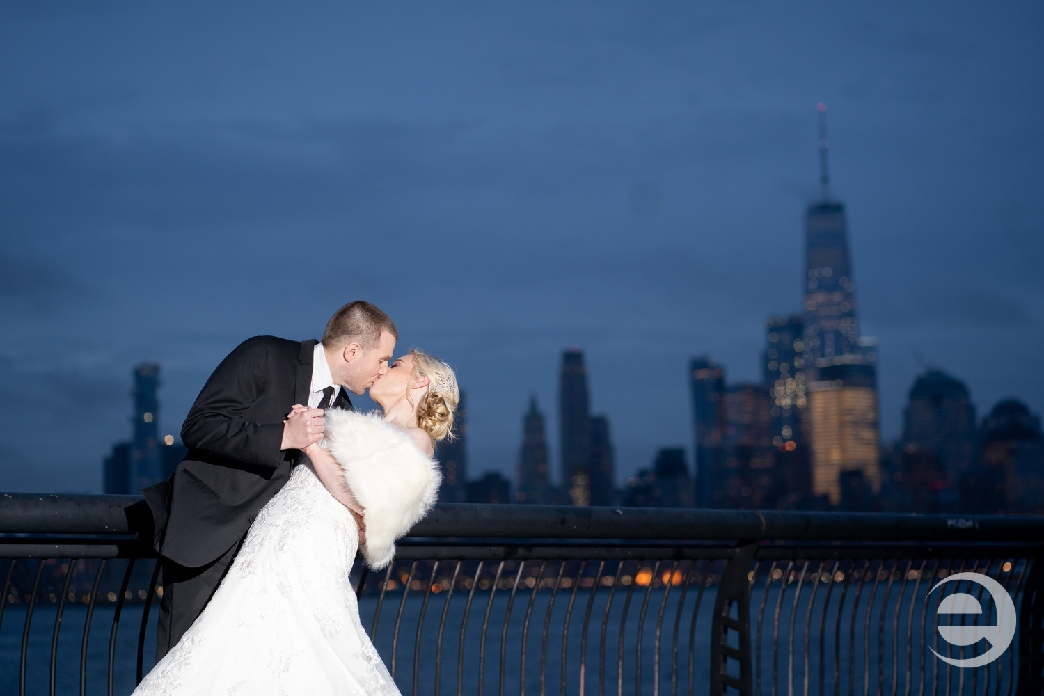 Married couple poses by waterfront for wedding photo