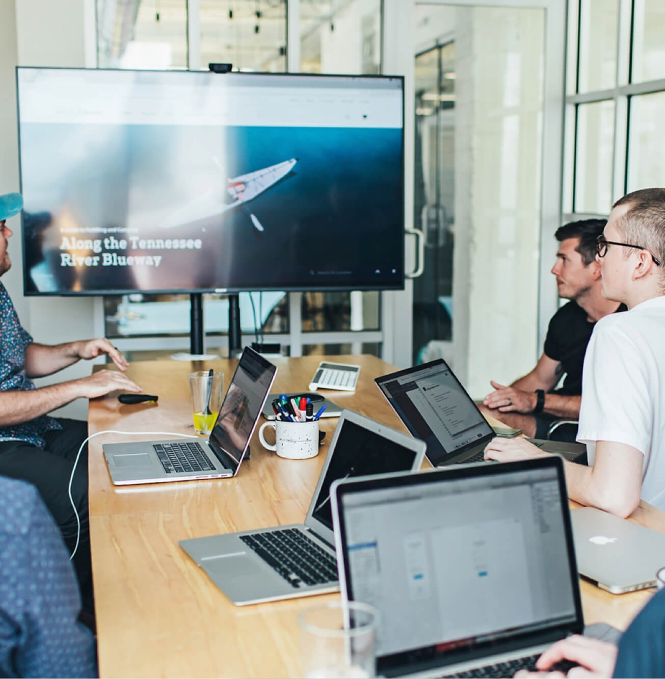 A group of creatives looking at a smart screen together