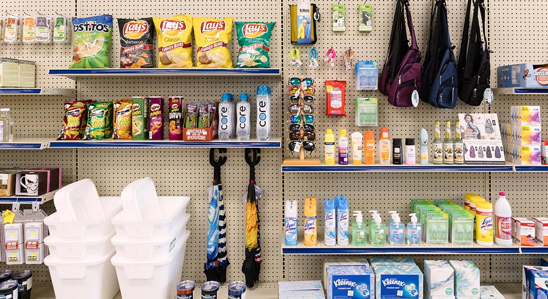St. Bernard Drugs convenience store items on a shelf, including snacks, sunglasses, cleaning supplies, bags, and more.