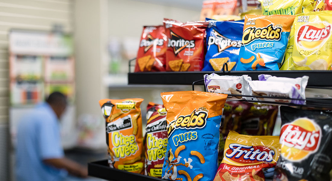Chips for sale at St. Bernard Drugs, including Doritos, Cheetos, Lays, Chee Wees, and Fritos.