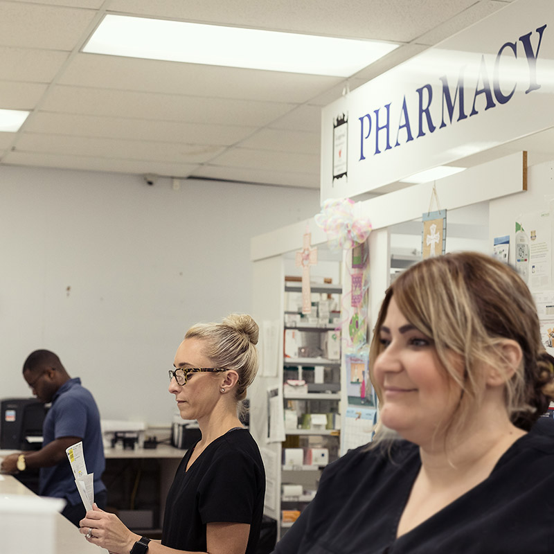 St. Bernard Drugs staff working behind the pharmacy counter