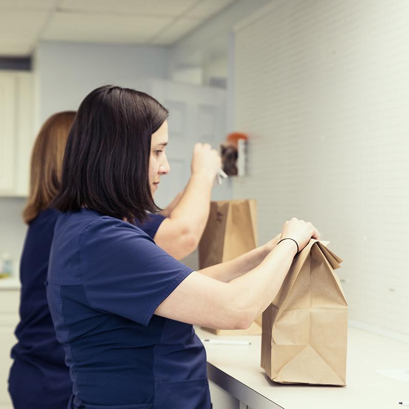 A St. Bernard Drugs staff member packaging a prescription.