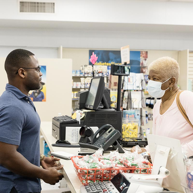A customer at St. Bernard Drugs having a consultation with a staff member.