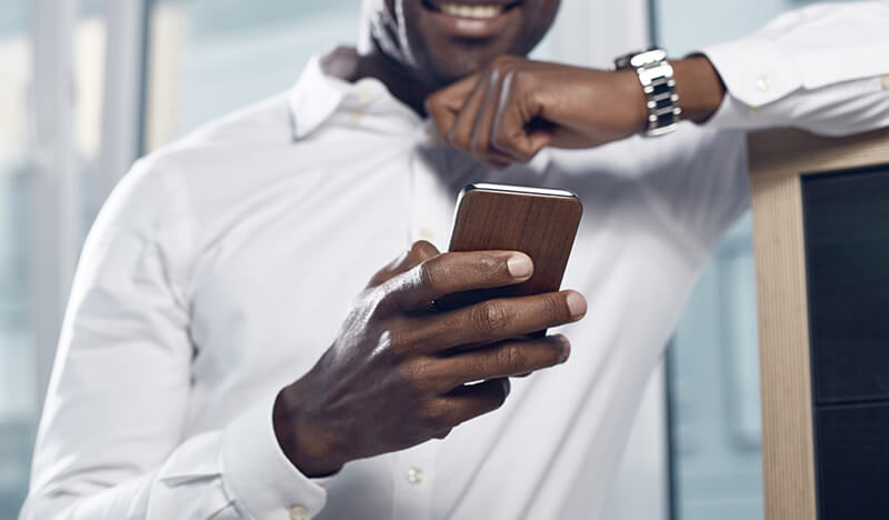 Image of  a man holding a mobile phone, which is focused in the foreground - OttoLearn Personalized Learning