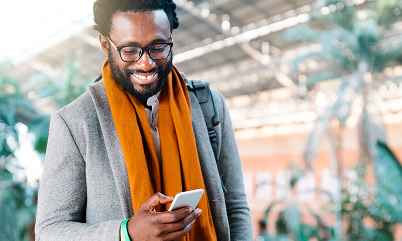 Image of a person in an orange scarf looking down at their phone - OttoLearn Personalized Learning