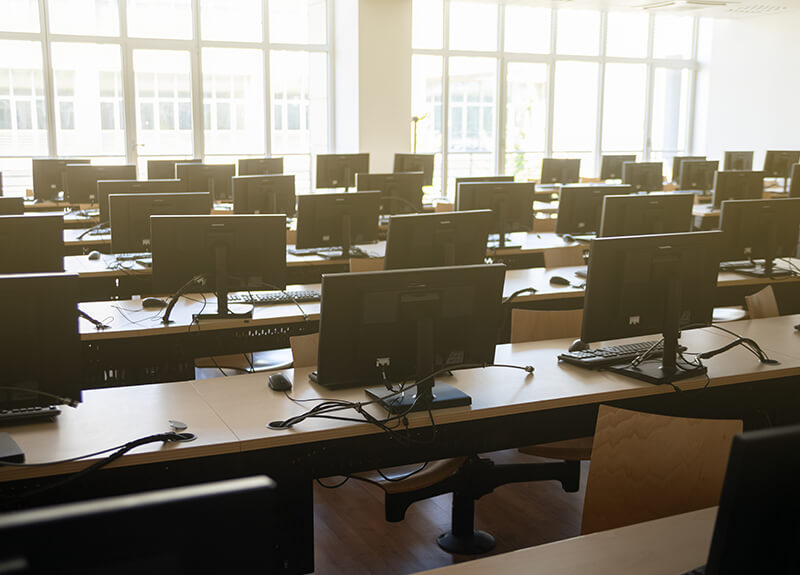 Image depicts an empty classroom. Monitors line several long tables on a backdrop of a window. - OttoLearn Microlearning