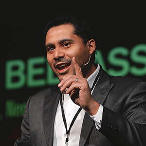 Dan Belhassen portrait - a man with short, black hair wearing a suit jacket with an open collar shirt passionately speaking to a crowd of people at an event