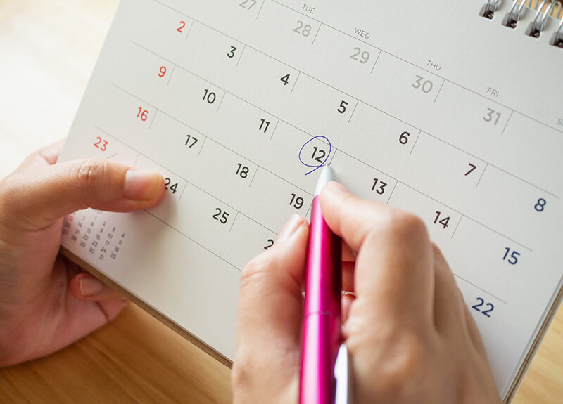 A hand holding a pen circles a date on a calendar - OttoLearn Microlearning