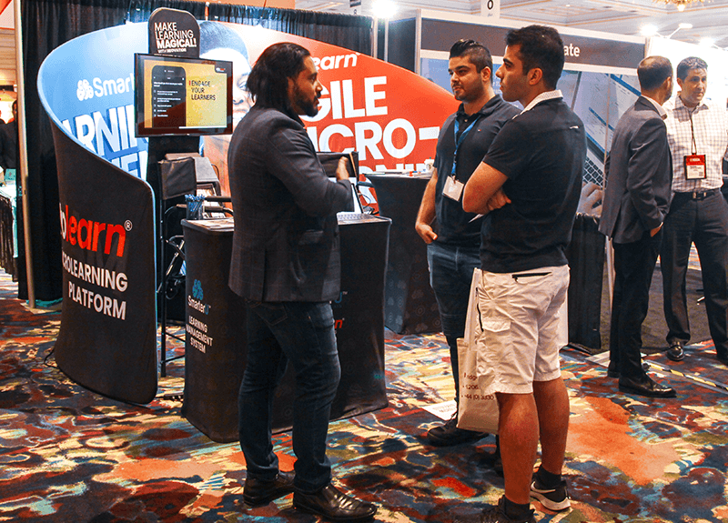 OttoLearn president Dan Belhassen talking with 2 men in front of the OttoLearn booth at DevLearn 2019 - OttoLearn Microlearning