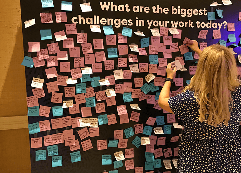 "A woman peels a sticky note off of a large board that asks ""What are the biggest challenges in your work today?"" - OttoLearn Microlearning"