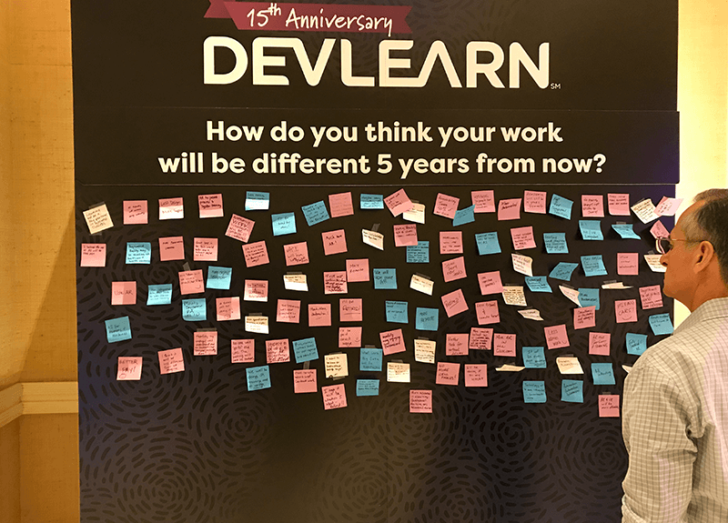 "A man looks at a large board full of sticky notes; the board asks ""How do you think your work will be different 5 years from now?"" - OttoLearn Adaptive Learning"