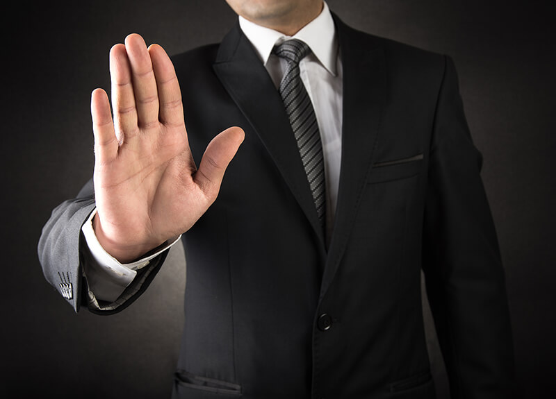 "Man in a black suit hold his hand out in a ""stop"" gesture - OttoLearn Microlearning"
