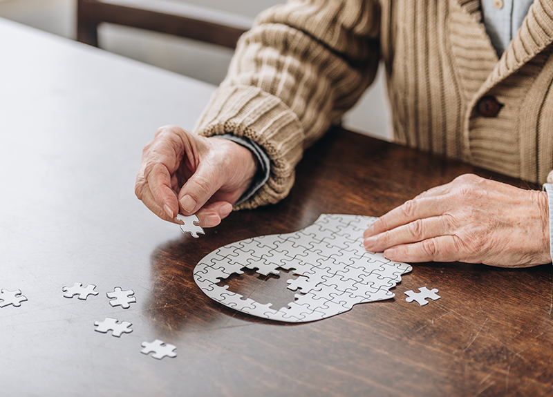 Elderly person putting a puzzle in the shape of a head together, pieces where the brain should be are missing - OttoLearn Adaptive Microlearning