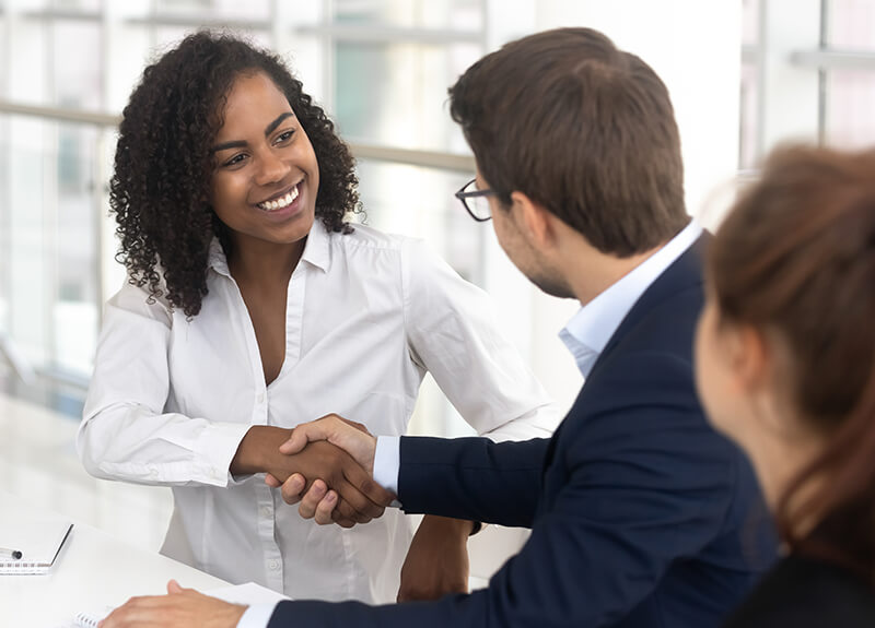 A smiling woman in a white buttoned shirt shakes hands with a man in a navy blue suit jacket - Corporate Training - Training Outcomes - OttoLearn Agile Microlearning