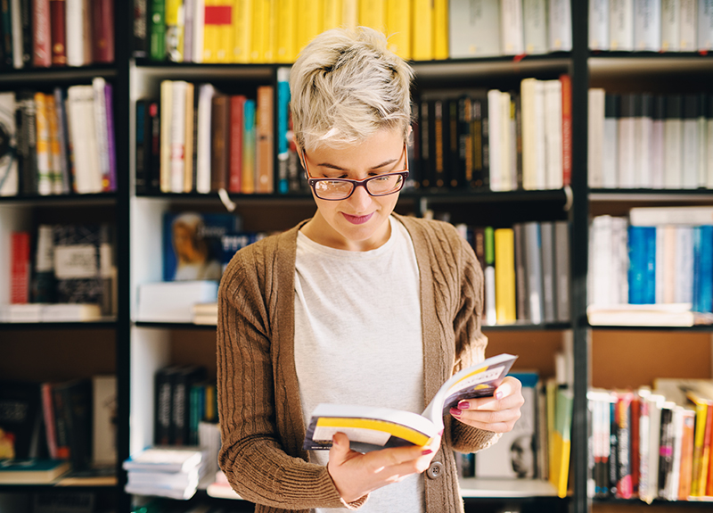 Adult woman wearing glasses and a brown cardigan reads a text book while standing in front of several shelves filled with books. Instructional Scaffolding - eLearning Best Practices - OttoLearn Agile Microlearning