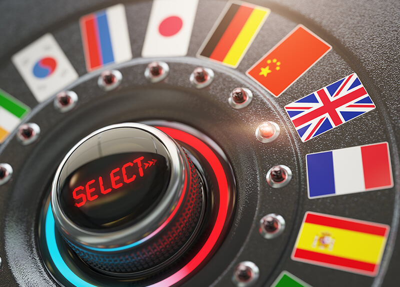 "A dial showing a series of country flags; the center of the dial says ""Select"" with arrows pointing out indicating a selected country flag."