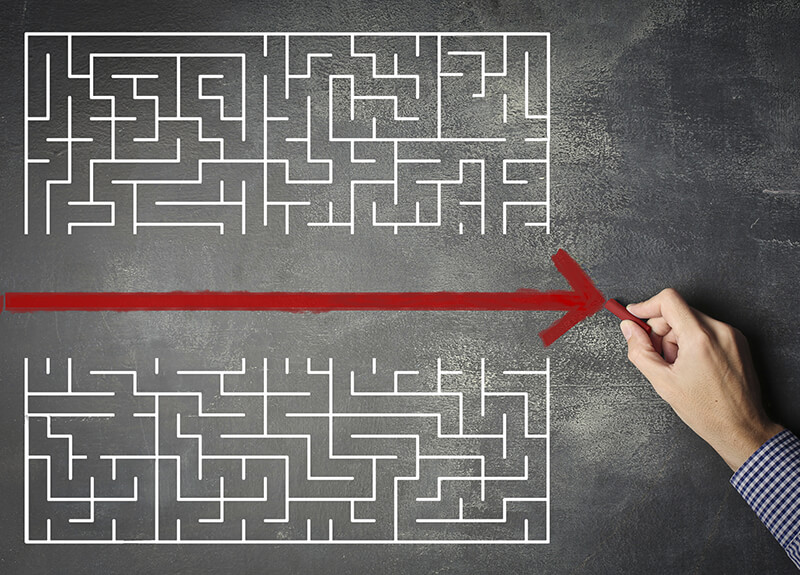 Drawing of a complex maze with a red arrow cutting it exactly in half.