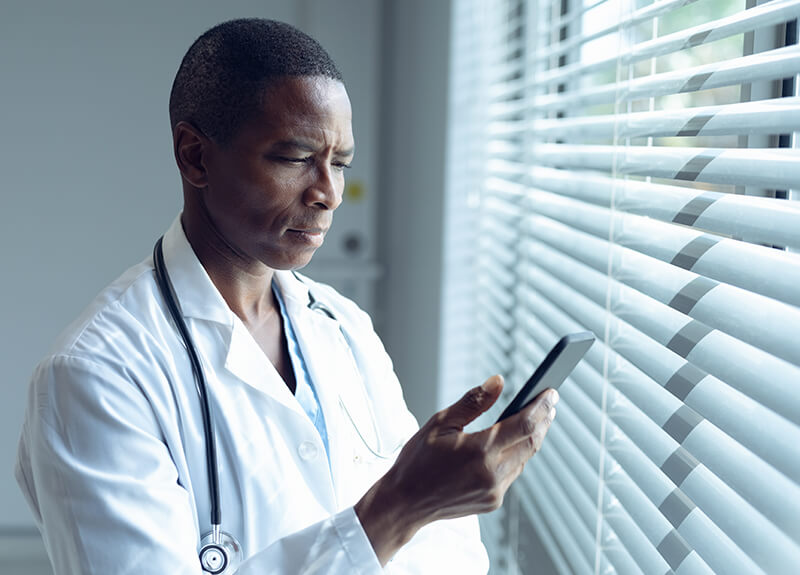 A doctor in a white labcoat with a stethoscope around his neck looks intently at is mobile phone.