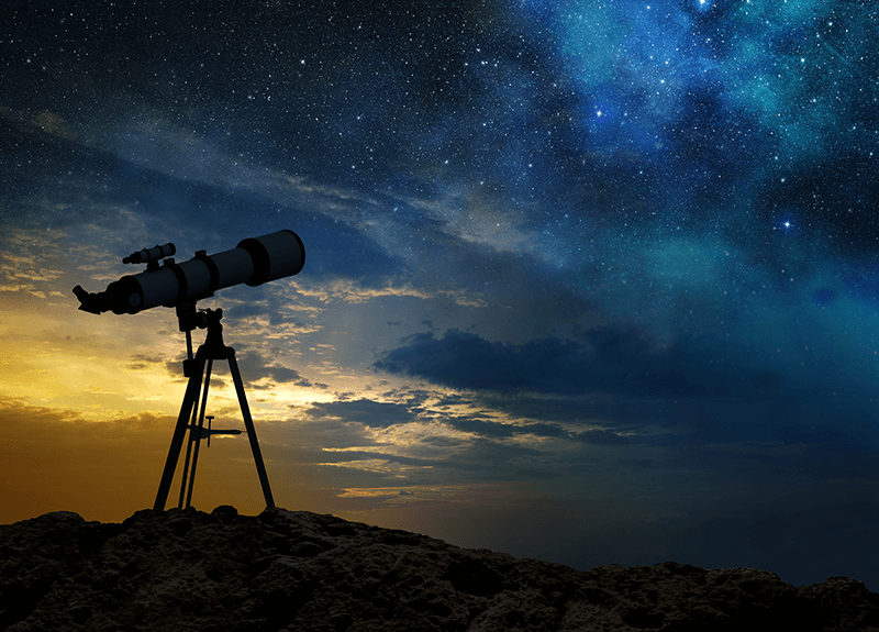 Image of a silhouetted telescope against a starry blue and yellow sky.