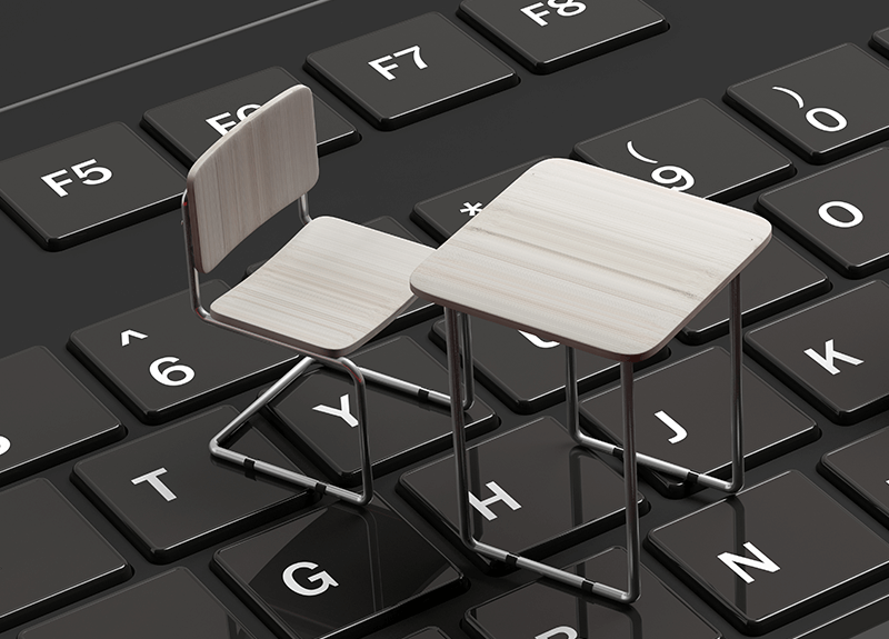 A tiny, white wood school desk and chair sit atop a large keyboard.