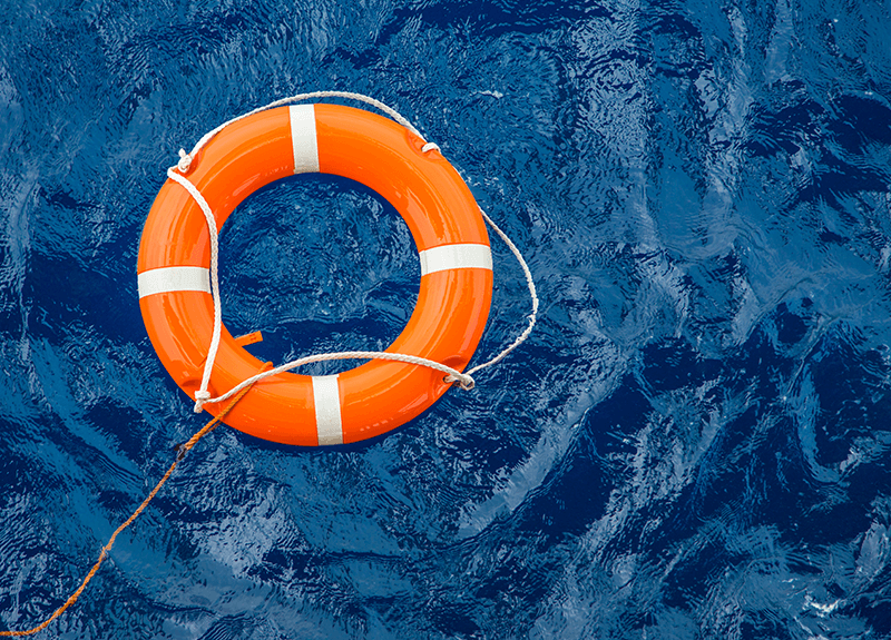 An orange and white life preserver ring floating on deep blue water.