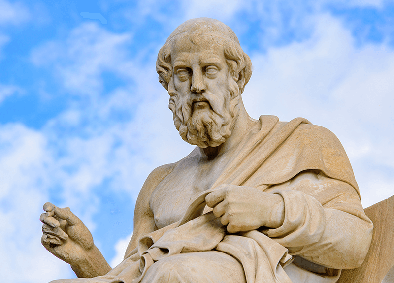 Close up of the statue of Plato against a blue, partly-cloudy sky.