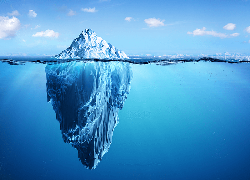 Iceberg floating in clear blue water, showing the lower half of the massive structure.