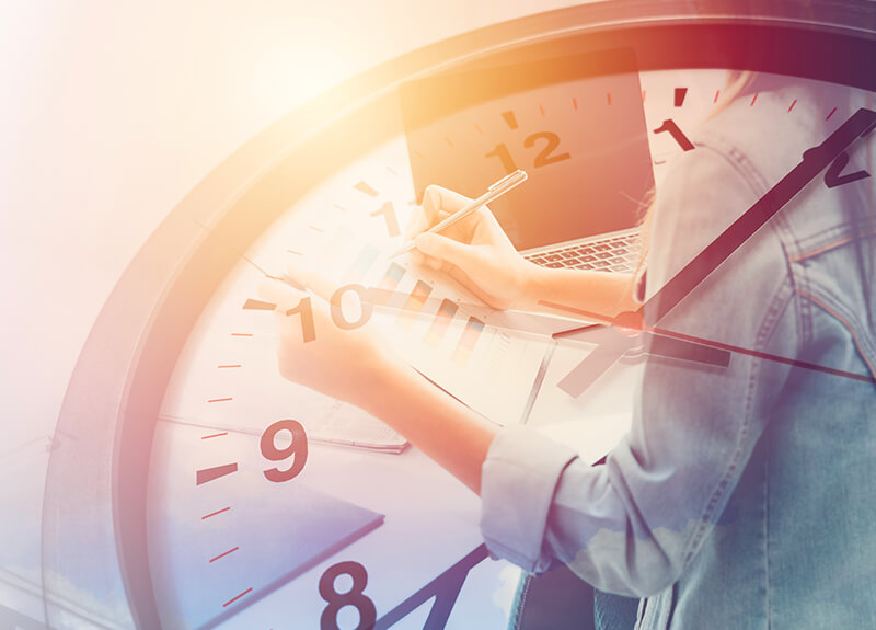 Close up of a clock with an image of an employee doing paperwork overlaid.