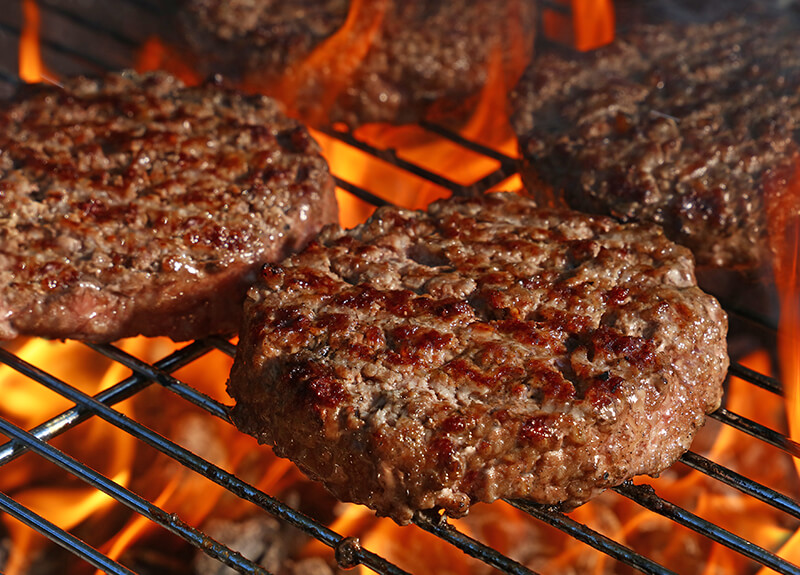 Beef burgers cooking on a flaming grill