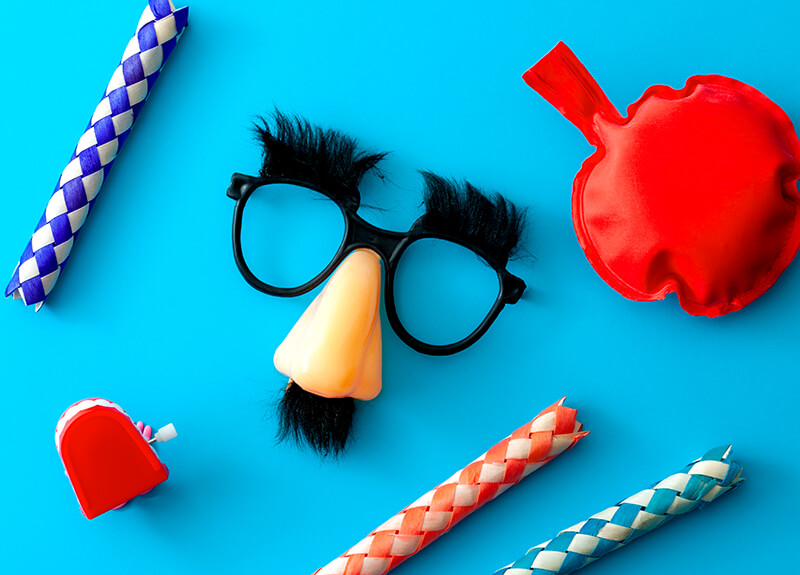 A series of novelty joke items on a sky blue background; three finger traps, a set of wind-up teeth, a whoopee cushion, and Groucho glasses.