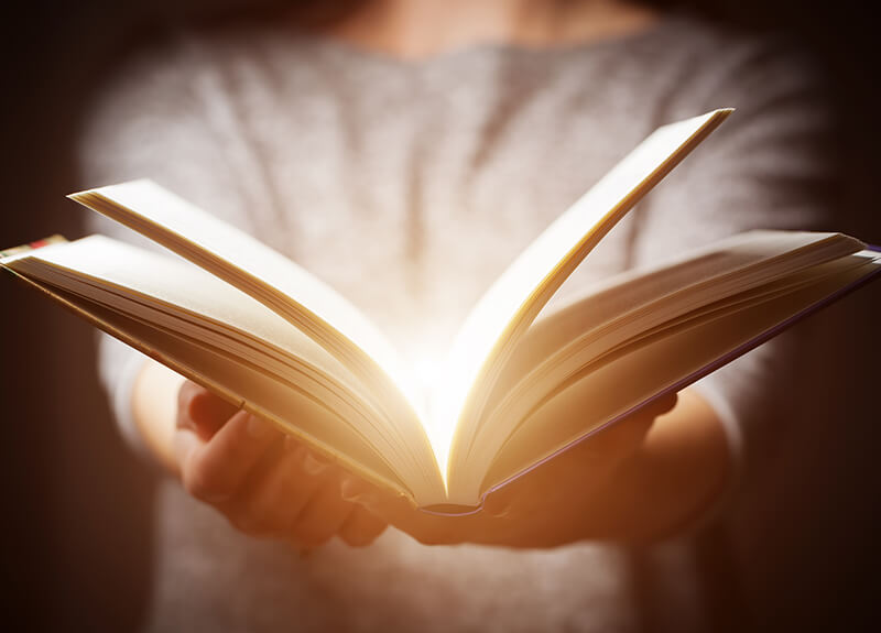 A person holding a open book out in front of them; from the middle of the book radiates a subtle yellow-white glow.