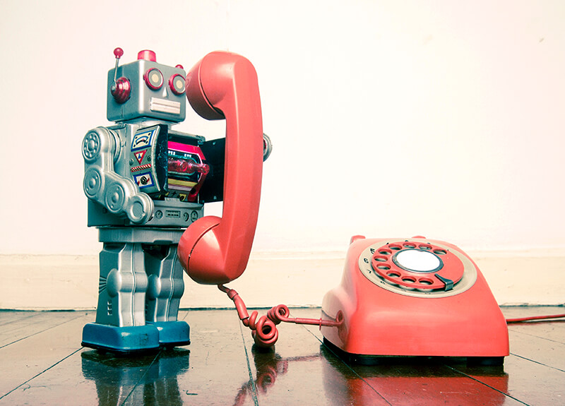 """A silver toy robot """"talking"""" on an old, red rotary phone."""