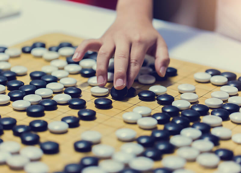 A close up of a Go board game. A hand is placing a black stone on the board.