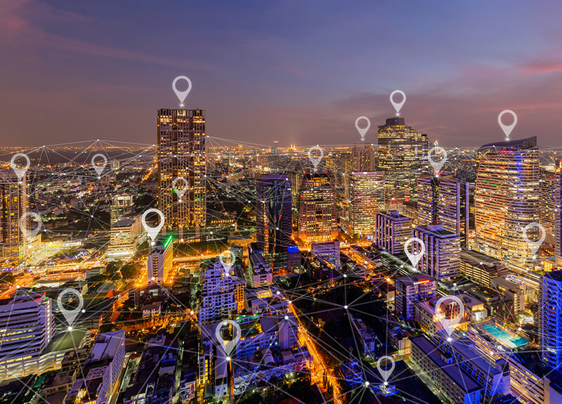 An overhead view of downtown Bangkok, Thailand at night with a series of thin, white lines all connecting to each other overlaid. At various points where the lines meet, white map pin markers appear.