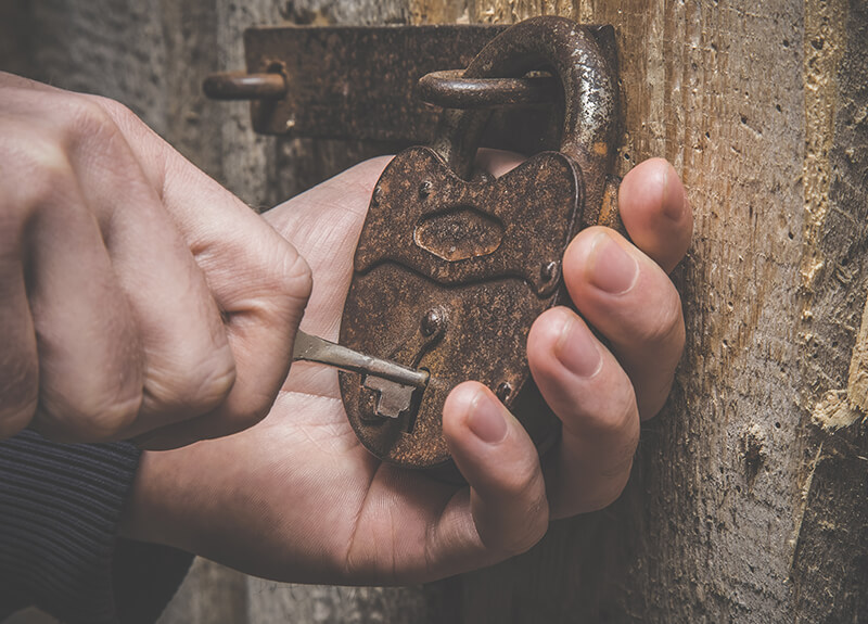 Close-up of a hand holding a rusty lock attached to a door. Another hand is putting a key into the lock.