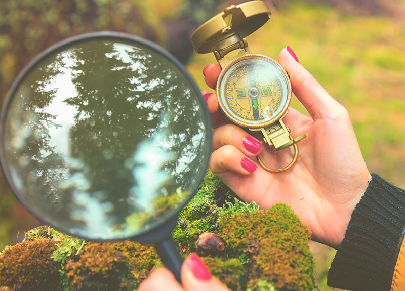A woman's hands on an earthy background - one hand is holding a compass, the other has a magnifying glass.