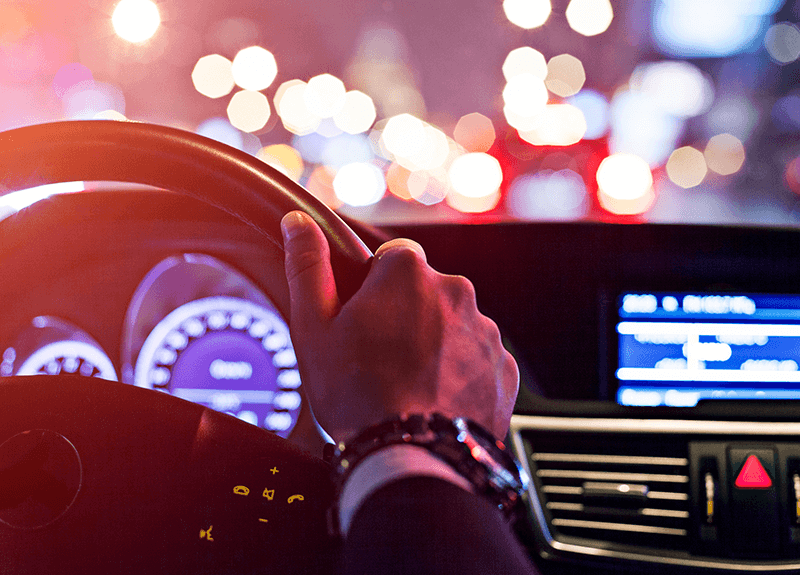 The inside view of a car behind the wheel. A man's hand grips the steering wheel while he drives the road at night.