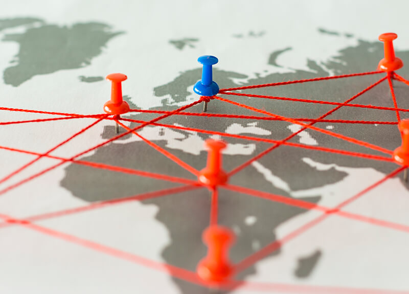 Close-up of a map focusing on Africa and Europe. There are various push pins stuck in the map and all are connected via thin, red string.