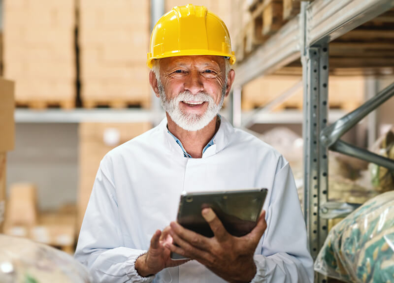 Smiling elderly man, wearing a yellow hard hat and a white jumpsuit, holding a tablet.