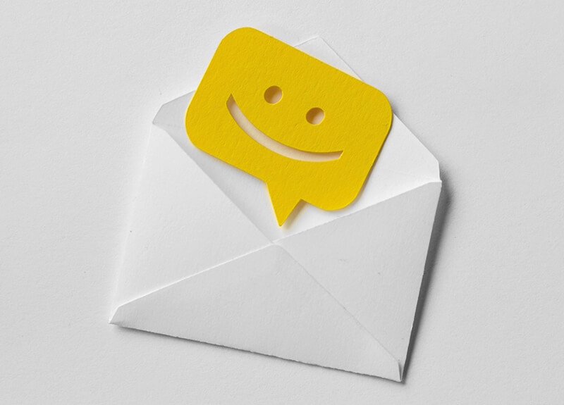 A open white envelope on a white background. A yellow paper speech bubble with a smiley face cut into it rests on top of the open envelope flap.