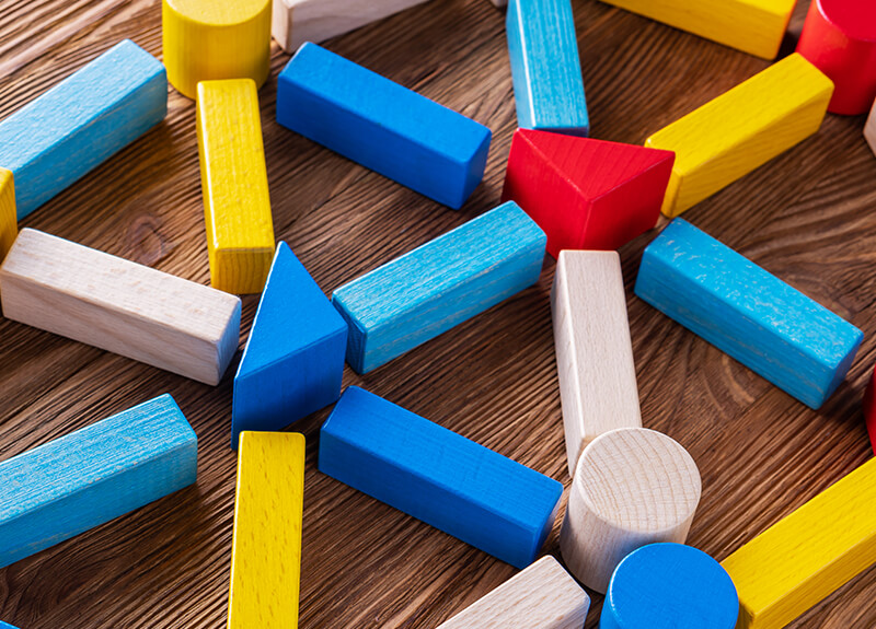 Colorful cylindrical and triangular wooden blocks laid out on a table, with wooden rectangles connecting to each one.