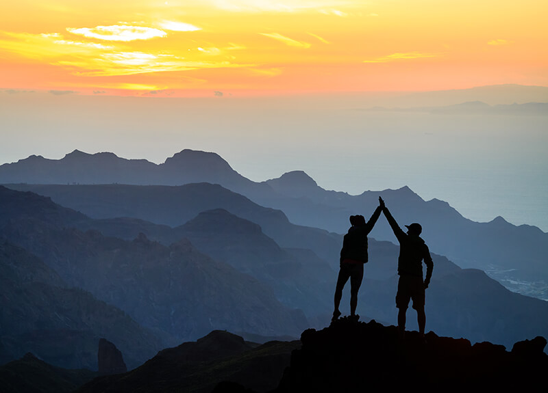 Two people high-fiving, silhouetted against a backdrop of mountains and a setting sun.