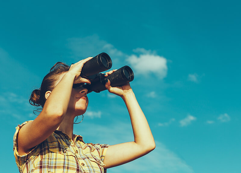 Young woman in a plaid shirt against a blue sky, looking through a pair of binoculars.