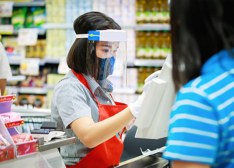 Grocery store clerk in a red apron, wearing a face mask, face shield and disposable gloves ringing people through the checkout.