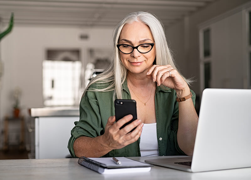Mature woman in glasses working from home, holding her phone in her hand, looking intently at the screen. In front of her sits her laptop and a notebook with a pen.