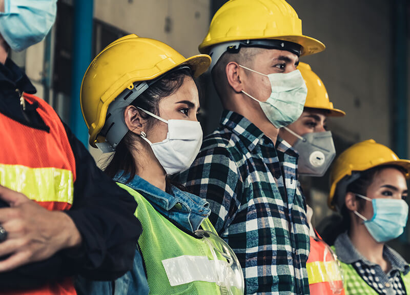 A group of construction workers standing in a line wearing face masks.