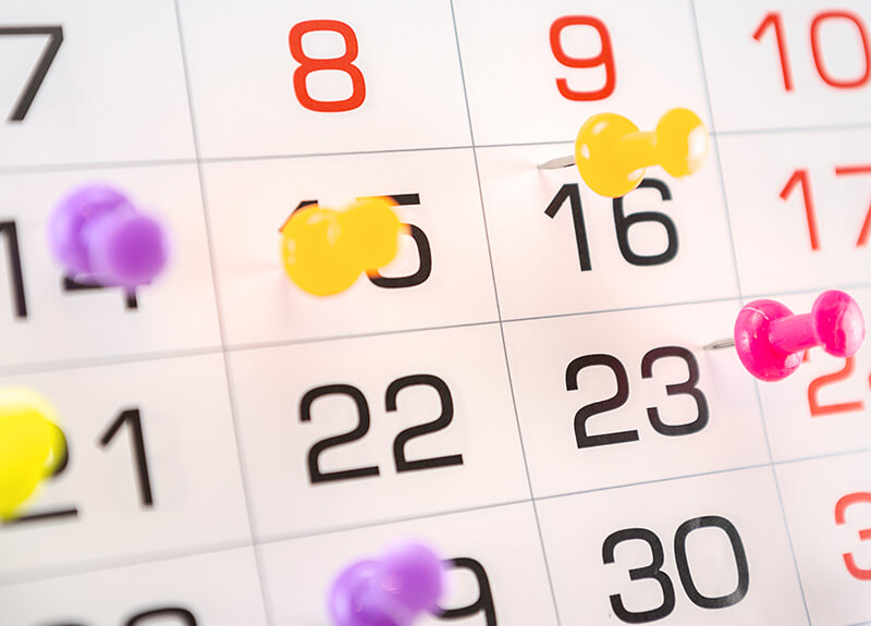 Close up of calendar days, some of which are marked with push pins of varying colors.
