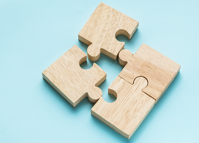 Four wooden puzzle pieces coming together on a pale teal background.