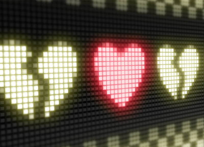 """A line of three pixelated hearts on a black background. The middle heard is solid with a red glow. The outer two hearts are """"broken"""" with a light green glow."""